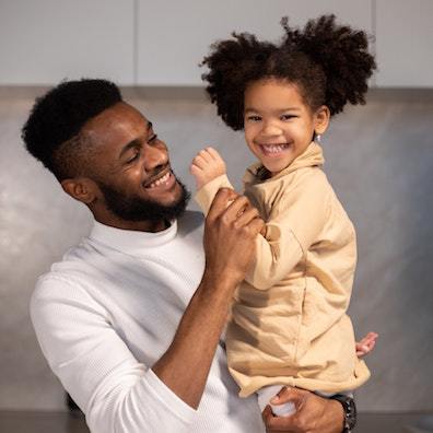 father holding daughter smiling