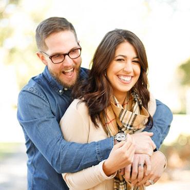 man standing behind woman hugging smiling