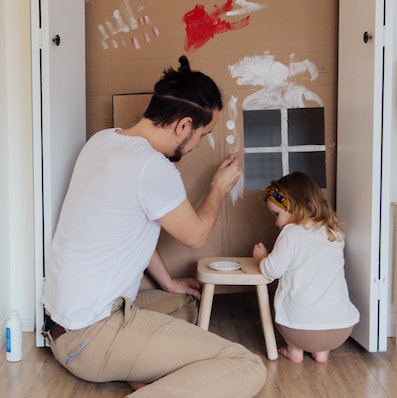 man and child painting cardboard house